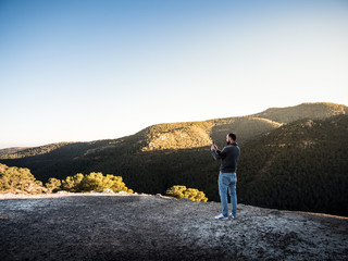 young man with beard takes a picture of a landscape