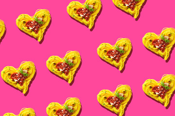 Pattern of hearts of pasta on pink background