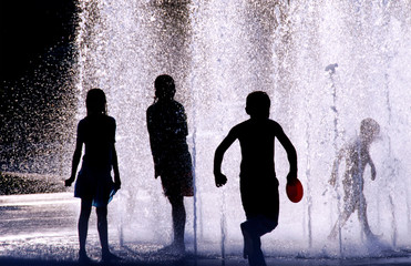 Silhouette of four children playing in a water fountain on a hot day, United States