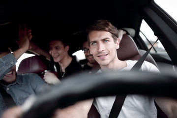 A group of people inside a car, on a road trip