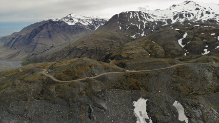 Aerial view of mountain road F985 leading to Joklasel and the Skalafellsjokull glacier, part of Vatnajökull National Park, Iceland. Panoramic landscape shot by drone camera.