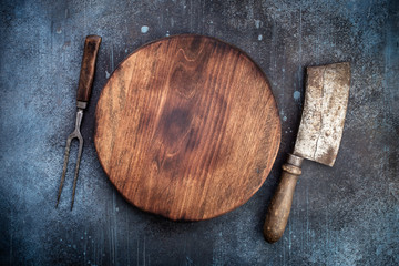 Round cutting board with vintage meat cleaver and fork on grunge concrete background with copy space