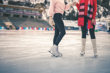 Unrecognizable teenagers girls ice skating outdoor at ice rink