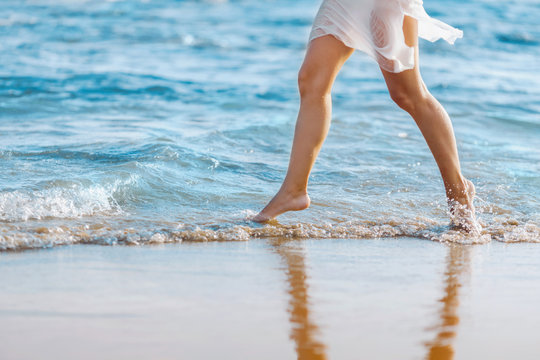 Beautiful young girl running on the beach barefoot in the water. Girl walking barefoot in the water at sunset.