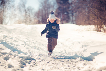 boy running on the path in the snowy park