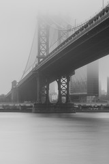 Black an white photo of Manhattan Bridge from east river on a foggy day with long exposure