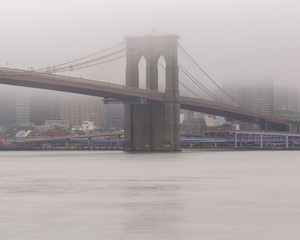 View on Brooklyn Bridge from east river on a foggy day with long exposure