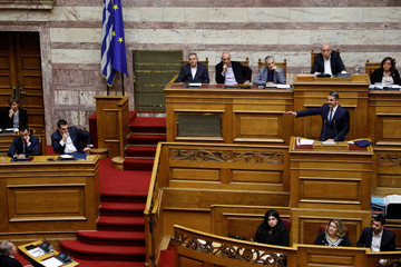 New Democracy party leader Mitsotakis addresses lawmakers as Greek PM Tsipras looks on during a parliamentary session before a confidence vote in Athens