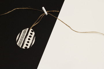 Decorated with napkin for decoupage egg on jute cord with clothespin on contrasting white and black background. Minimalism style.