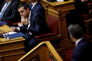 Greek Prime Minister Alexis Tsipras looks on as New Democracy party leader Kyriakos Mitsotakis addresses lawmakers during a parliamentary session before a confidence vote in Athens