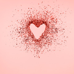 Glitter heart dissolving into pieces on pink background.  Valentines day, broken heart and love emergence concept. Coral color