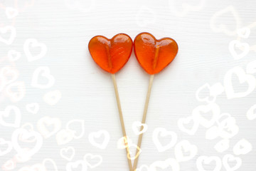 Candy hearts. Two heart shaped lollipops isolated on white wooden background. Valentine`s day, background. Copyspace.