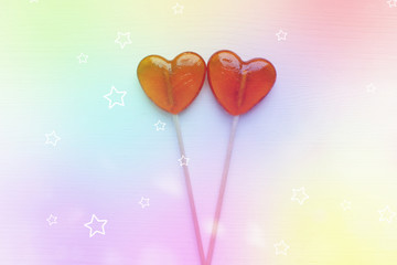 Valentine's day background. Two lollipops on a heart-shaped stick isolated on pink background, bokeh effect. Copy space, top view