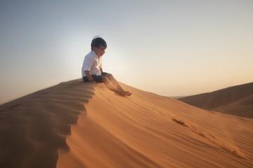 boy sitting on the sand dune