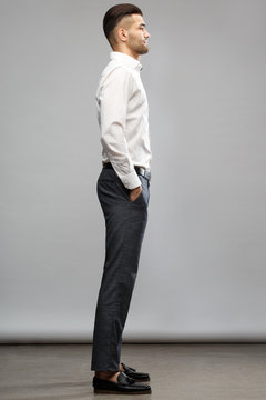 An elegant man in casual business clothes is standing tall with his hands in his pockets on a gray background, side view.
