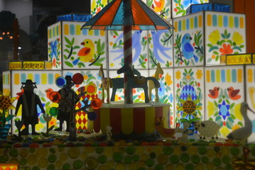 Glowing caramel houses and caramel figurines of the cityscape with animals, residents and city cultural attractions