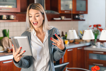 Young happy woman using tablet while drinking red wine in kitchen