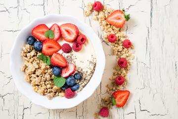 Breakfast with granola with berries, yoghurt and fruits. Cereal oatmeal with strawberries, blueberries and raspberries. Muesli with fruits and berries. Dieting, healthy food concept