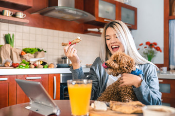 Young happy woman sitting at table and eating breakfast while holding a dog in her lap in kitchen