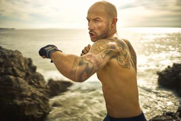 man boxing overlooking ocean