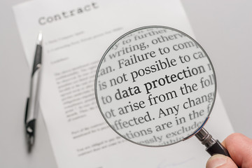 Data protection regulations of a contract are checked carefully with a magnifying glass