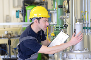 Fitter checks a technical plant in an industrial plant  // Monteur kontrolliert eine technische Anlage in einer Industrieanlage