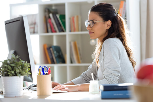 Pretty young business woman working with her computer in the office.