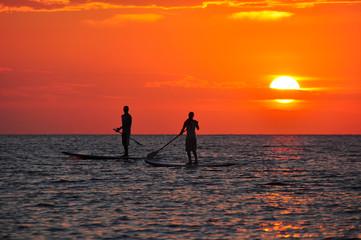 Personas practicando paddle surf al atardecer en Ibiza