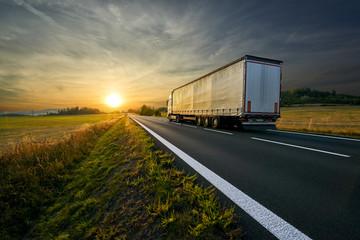 Fotobehang - Truck on an asphalt road running towards the sunset in rural countryside