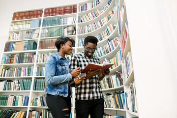 young Afro-American students reading book between the shelves in the library