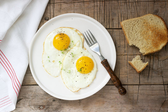 Breakfast of fried eggs, bread toasts and coffee on a wooden table. Rustic style.