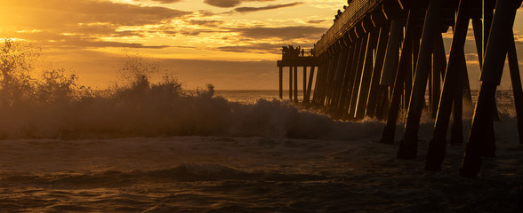 Waves breaking under the pier at Hermosa Beach, California. Tourists and visitors silhouetted against cloudy sunset sky