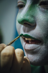 Youn woman putting lipstick, green color, face paint