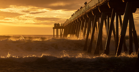 Large backlit waves breaking under the pier at Hermosa Beach, California. Tourists and visitors silhouetted against cloudy sunset sky