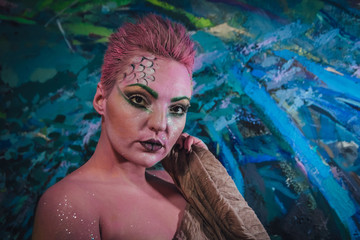 Beautiful pink hair female colored with face paint, creative makeup