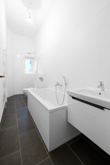 white bathroom with bathtub and shower after renovation