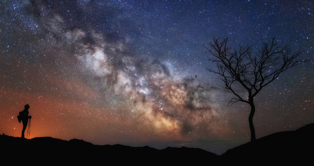 Woman looking at the stars, Milky way and tree. Scenery Landscape with night starry sky and silhouette of standing happy woman. Milky way Galaxy with traveler. Universe.