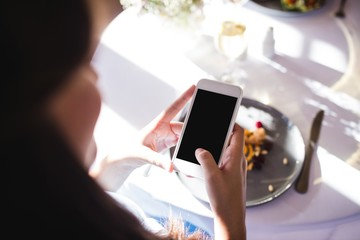 Woman clicking photo of a food on plate