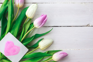 White and purple tulips on a white wooden background. Spring. International Women's Day. Valentine's Day. card with watercolor hearts,Selective focus.