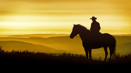 A cowboy on horseback observes the golden mountains
