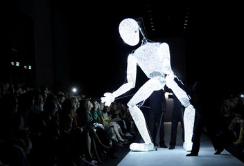 An illuminated figure performs during the presentation of creations by Riani during the Berlin Fashion Week Autumn/Winter 2019/20 in Berlin