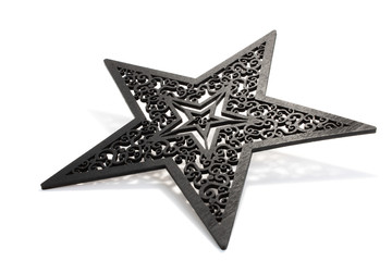 Black star as Christmas decoration made and cut out with laser from wood