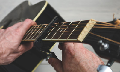 man sets the capo on the guitar