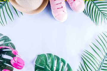 Colorful summer vacation and holiday flat-lay. Straw hat, sunglasses, palm and monstera leaves on bright blue yellow background, top view, copy space banner