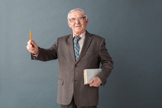 Senior man teacher wearing glasses studio standing isolated on gray with book pointing up solution looking camera illuminated