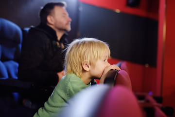 Cute little boy with his father watching cartoon movie in the cinema