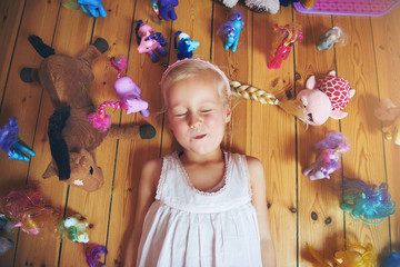 Girl with eyes closed lying in toys