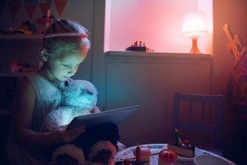 Little girl browsing tablet pc with bear