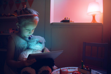 Little girl with bear using tablet pc