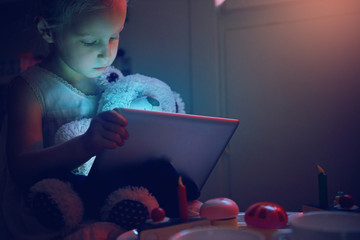 Little girl with toy bear browsing tablet